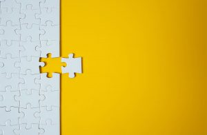 a Jigsaw on yellow background with one piece removed