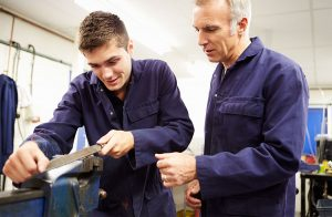 Older man watches younger man working on a vice